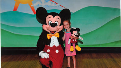 Ariah Rogers, 5, is with Mickey Mouse at Disney World. She went to Disney World with her family through the Make-A-Wish foundation and Give Kids the World resort.