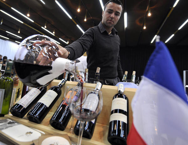 A Bosnian presenter pours a glass of French Bordeaux wine at the First Sarajevo Wine Festival, in Sarajevo.