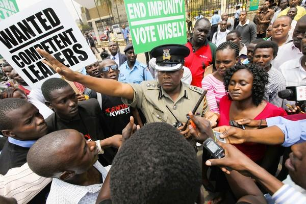 Kenyan protesters confront a police officer in Nairobi during a demonstration over parliamentary wages.