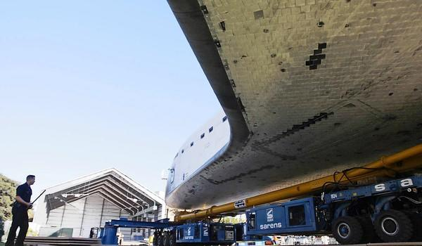 After its 12-mile crosstown journey from Los Angeles International Aiport, space shuttle Endeavour is guarded by a lone LAPD officer as it sits outside its temporary hangar at the California Science Center in Exposition Park.