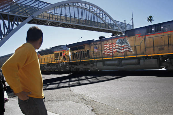 Luis Luna anxiously watches a U.S.-bound freight train move slowly through downtown Nogales, Mexico. He wants to hide underneath one of its cars and stowaway across the border into Arizona. After nearly all his life living in America, the Mexican citizen was deported 8 months ago from his home in Washington state.