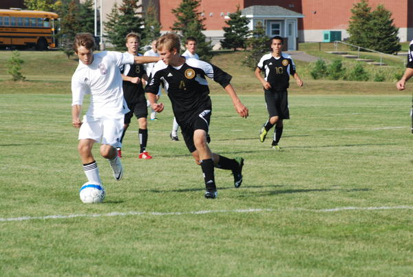 Charlevoix's Walker Drost (left) dribbles the ball away from Harbor Springs' Mitch Corey during a Lake Michigan Conference match earlier this season. Both the Rams and Rayders open district play today, Monday, as Harbor Springs faces Harbor Light Christian at 4 p.m. at the Click Road Soccer Complex, while Charlevoix plays host to Leland at 5 p.m.