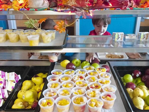 Meriden's Hanover Elementary School student Christian Rivera grabs an apple from the fruit section of Hanover's cafeteria Friday. Connecticut Schools are figuring out how to meet new standards for healthy lunches.