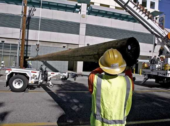 Glendale Water & Power workers prepare a new pole to replace one that was damaged by a vehicle on Harvard between Louise and Maryland in Glendale on Thursday, February 9, 2012.