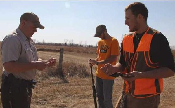 Wildlife Conservation Officer Nick Cochran, left, checks the hunting licenses of NSU students Kraig Nelson, center, Derek Tymeson during a resident only hunting day.