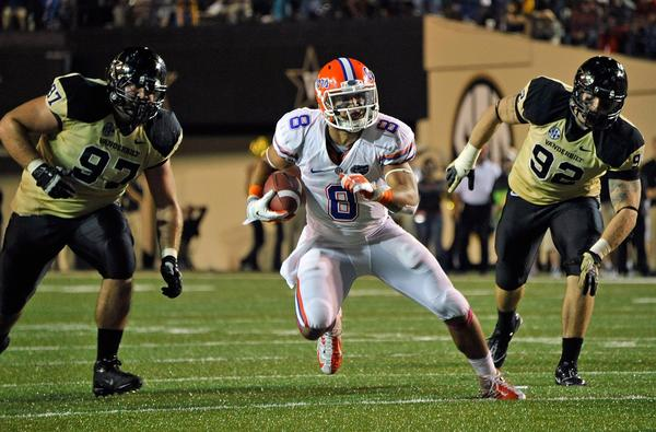 Trey Burton #8 of the Florida Gators runs between Jared Morse #97 and Kyle Woestmann #92 of the Vanderbilt Commodores at Vanderbilt Stadium on October 13, 2012 in Nashville, Tennessee.