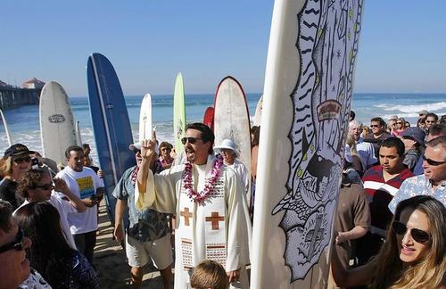 "Surfer and Catholic priest Tom Munoz joins scores of people on the beach as they sing ""God Bless America"" at the conclusion of the Fifth Annual Blessing of the Waves at the Huntington Beach Pier on Sunday. An interfaith service sponsored by the Roman Catholic Diocese of Orange, the event merges surfing and spirituality. Sunday's event attracted several hundred participants, and featured speakers from the Jewish, Christian, B'hai and Islamic faiths. After the service, about two dozen boarders took to the surf, which measured 3 to 5 feet with fair shape."