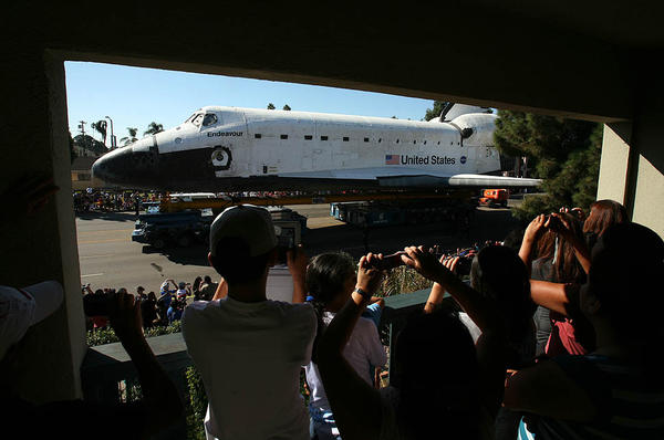 The Gonzalez family watches the space shuttle Endeavour from their balcony in the 1300 block of West Martin Luther King Blvd.