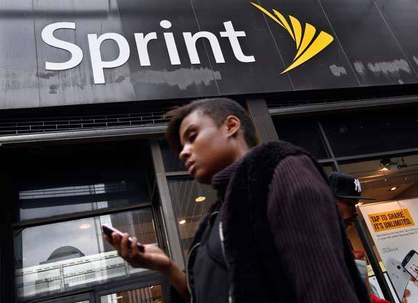A woman uses her phone as she walks past a Sprint store in New York's financial district. Japanese mobile operator Softbank Corp said it will buy about 70 percent of Sprint Nextel Corp, the third-largest U.S. carrier, for $20.1 billion - the most a Japanese firm has spent on an overseas acquisition.