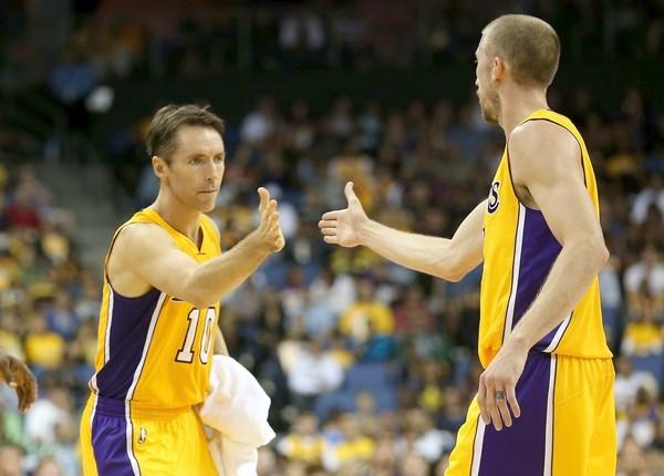 Lakers point guard Steve Nash high-fives teammate Steve Blake as he enters the preseason game against the Trail Blazers.