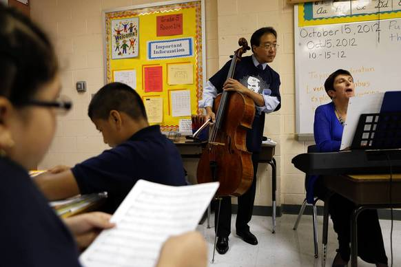 Yo-Yo Ma, center, and music teacher Linda DeGuzman practice musical selections in a fifth grade classroom at Manuel Perez Jr. Elementary School in Chicago's Pilsen neighborhood on Monday, Oct. 15, 2012.