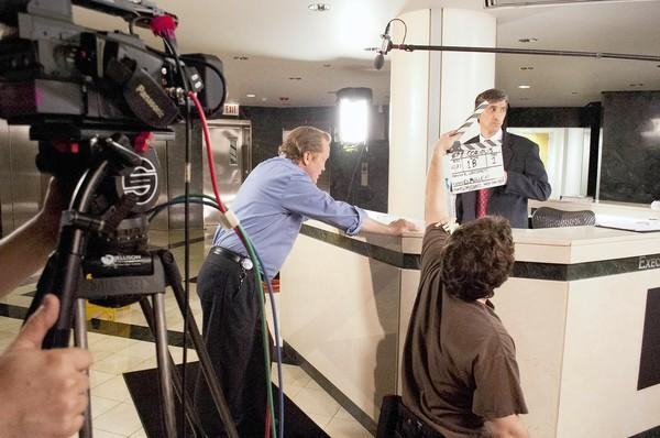 "Actors Christian Stolte, left, and David Pasquesi, right, get ready for a take as Alex Malm holds the cue card during a scene from ""Graveyard."""
