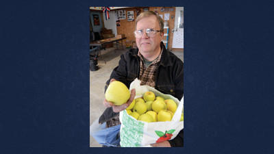 Tim Airersan of Airesman Orchard, Inc. sits on empty apple crates with the last half-dozen apples the business has left from this season.