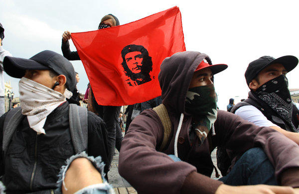 "Masked protesters attend a march in Bogota, Colombia, demanding to participate in the government's peace talks with the rebels of the Revolutionary Armed Forces of Colombia, or FARC. One holds an image of Cuba's revolutionary hero Ernesto ""Che"" Guevara."