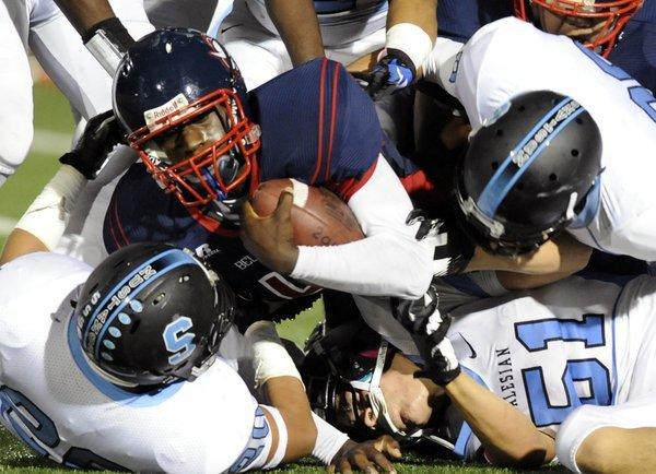 Bell-Jeff's Jalen Henry is taken down by Salesian defense.