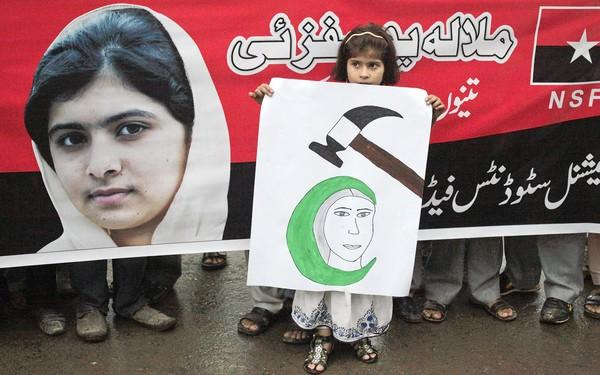 A girl holds a placard next to an image of schoolgirl Malala Yousufzai, who was shot by the Taliban, during a rally in Lahore, Pakistan.