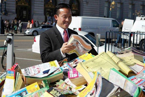 "San Francisco Board of Supervisors President David Chiu looks through a pile of phone books in the back of a pickup truck during a news conference in San Francisco last year. Chiu, a sponsor of the city's phone-book law, said Monday's ruling ""protects giant corporate polluters that litter our city doorsteps with millions of unwanted Yellow Page books."""