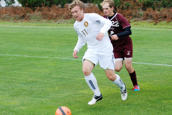 Harbor Springs' Forrest Lundgren (left) dribbles the ball away from Harbor Light Christian's Jacob Anderson during Monday's Division IV district quarterfinal at the Click Road Soccer Complex. The Rams defeated the Swordsmen, 2-1.
