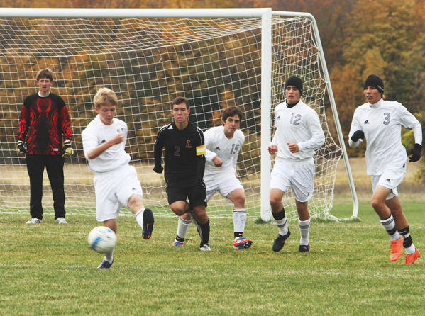 Charlevoix's Brendan Britt (second from left) clears the ball from in front of Charlevoix goalkeeper Ryan Joy (left) as teammates Jordan Jelinek (15), Justin Pearl (12) and Nick Snabes (3) look on Monday during a Division IV district quarterfinal match at the Charlevoix High School soccer field.