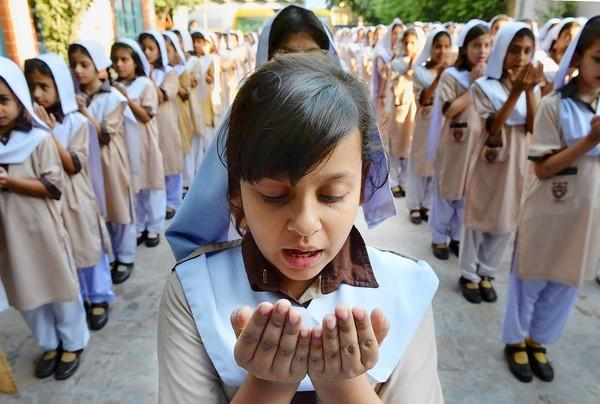Pakistani school girls pray for the early recovery of child activist Malala Yousafzai, who was shot in the head in a Taliban assassination attempt.