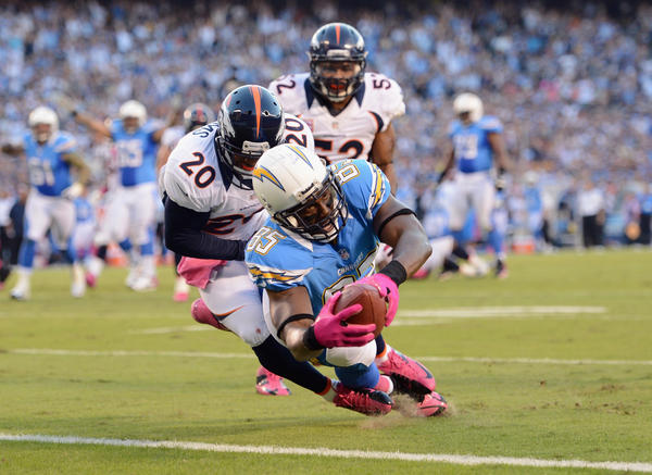 Antonio Gates #85 of the San Diego Chargers dives into the endzone for a touchdown in the first quarter past Mike Adams #20 of the Denver Broncos during the NFL game at Qualcomm Stadium on October 15, 2012 in San Diego, California.