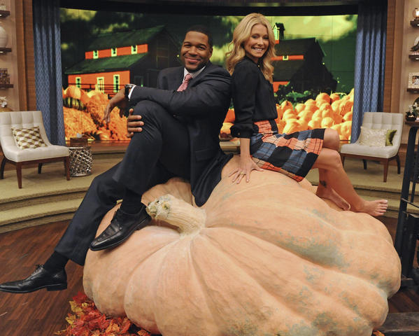"Kelly Ripa and Michael Strahan sit on the ""World's Largest Pumpkin"" during an appearance on ""LIVE with Kelly and Michael,"" on the set at WABC in New York."