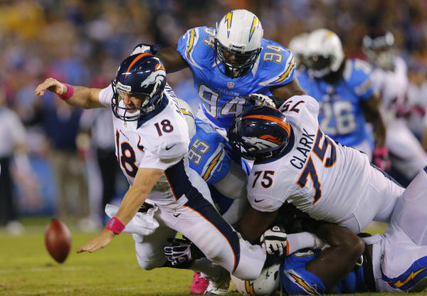 Denver Broncos quarterback Peyton Manning is brought down by San Diego Chargers' Shaun Phillips and Corey Liuget during their Monday game in San Diego