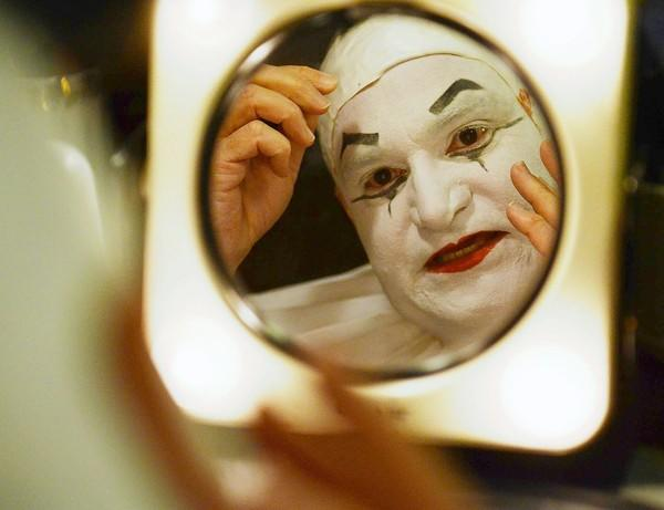 Steve Bauer, of Lutherville, who plays the Timoniac clown, checks his hair piece in the mirror.