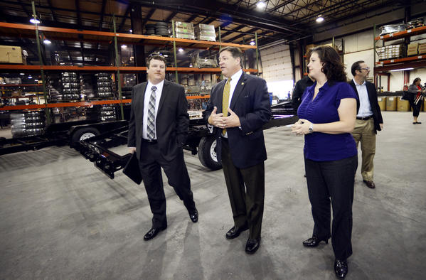 From left, Andy Gehman with the National Association of Trailer Manufacturers, U.S. Rep. Bill Shuster and Sandy Poffenberger, president of CAM Superline, walk through CAM's trailer-manufacturing facilities Tuesday morning in Zullinger, Pa.
