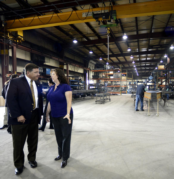 U.S. Rep. Bill Shuster and Sandy Poffenberger, president of CAM Superline, talk during a tour of CAM's trailer-manufacturing facilities Tuesday morning in Zullinger, Pa.