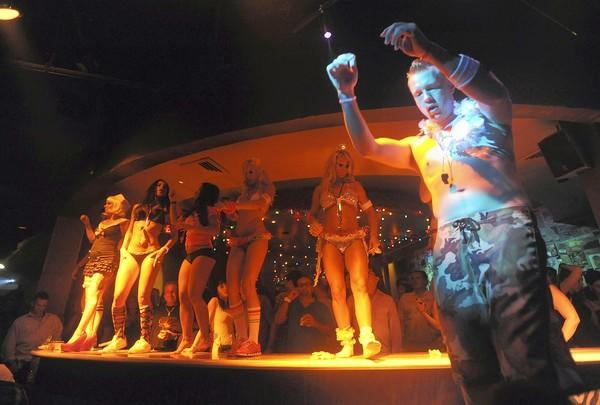 Bikini-clad bartenders dance on top of the bar at the Baja Beach Club in Boca Raton.