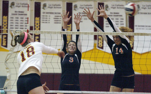 La Canada's Micaela Anderson, from left, spikes the ball as South Pasadena's Jessica Arroyo and Claire Kieffer-Wright attempt to block the spike during a game at La Canada High School on Tuesday, October 16, 2012.