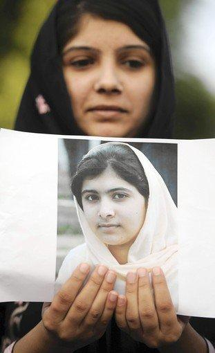 An activist holds a photo of Malala Yousufzai, 14, who was shot by the Taliban.