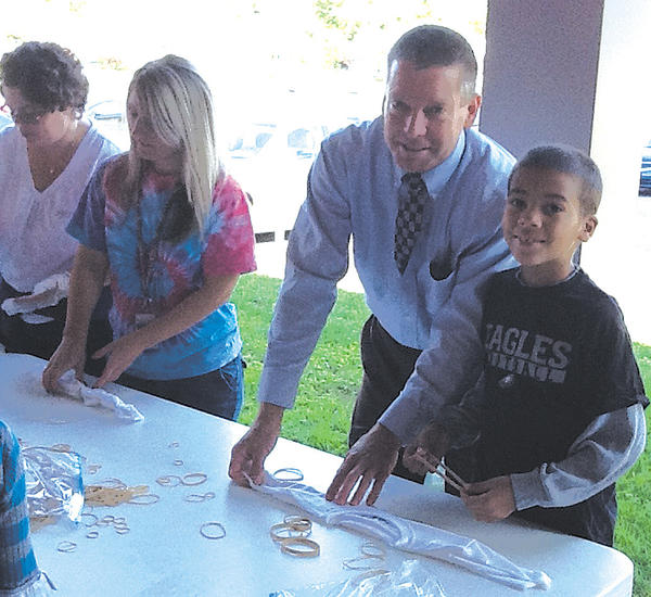 During a recent visit to Salem Avenue Elementary, Deputy Superintendent of Schools Boyd Michael took time to help second-grader Mekhi Fisher tie dye a shirt during the school's monthly Positive Behavior Intervention and Support activity. Also shown helping are parent volunteer Terra Bennett, far left, and teacher Brittany Sprecher.