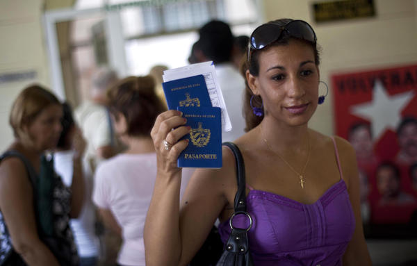 A woman shows her passport and that of her son to reporters as she leaves an immigration office in Havana, Cuba, Tuesday. The Cuban government announced Tuesday that it will no longer require islanders to apply for an exit visa, eliminating a much-loathed bureaucratic procedure that has been a major impediment for many seeking to travel overseas for more than a half-century.