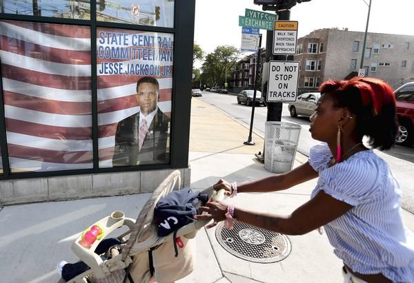 A woman pushes a stroller past Rep. Jesse Jackson Jr.'s office on Chicago's South Side. A gossip site reported two sightings of the convalescent congressman at a bar in the nation's capital last week.