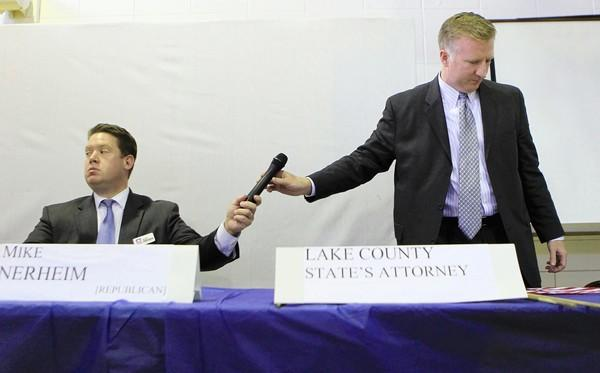 Lake County State's Attorney's candidates , Mike Nerheim (R), left, and Chris Kennedy (D), right, pass a microphone to each other during a candidate's forum at Most Blessed Trinity Church in North Chicago on Sunday, Oct. 14, 2012.