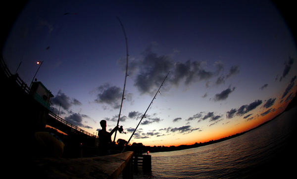 A fisherman casts his line into the Halifax River at High Bridge, at the east side of the Tomoka Marsh Aquatic Preserve, north of Ormond Beach, Thursday, October 11,  2012.