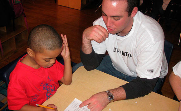 A United Way volunteer assists a student with math homework as part of the organization's early literacy focus.