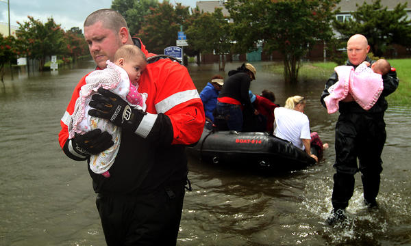 Newport News firemen Corey Archer and Jermiah Johnson carry babies from a boat at City Line apartments after heavy rain caused flooding in the area.