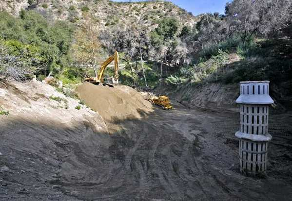 L.A. County Public Works crews remove debris from the Mullally debris basin at the end of Manistee Drive in the Paradise Valley neighborhood in La Canada Flintridge in 2010. Officials are planning a drainage tunnel from the basin to Pickens Canyon.