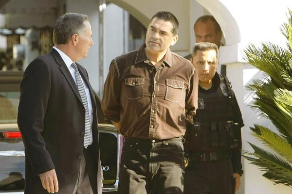 Los Angeles County Assessor John Noguez is taken into custody by investigators with the Los Angeles County district attorney's office outside his Huntington Park home. The assessor is accused of taking bribes from a prominent property tax consultant.