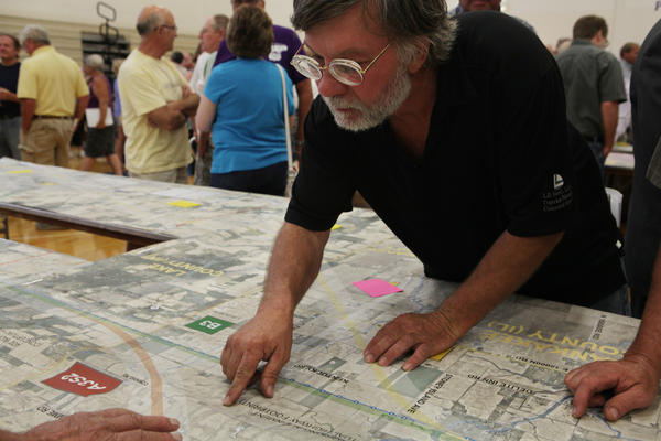 Chris Persch looks at a section of map outlining the Illiana Tier 1 Draft Environmental Impact Statement at at Peotone High School in Peotone, Ill.
