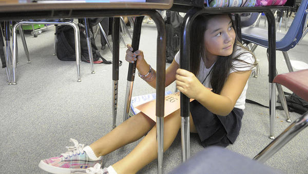 "Sixth-grader Giselle Barroso participates as an injured student with a ""broken leg"" as she waits for a search and rescue team during The Great California ShakeOut earthquake drill at Jefferson Elementary School on Oct. 20, 2011, in Calexico."