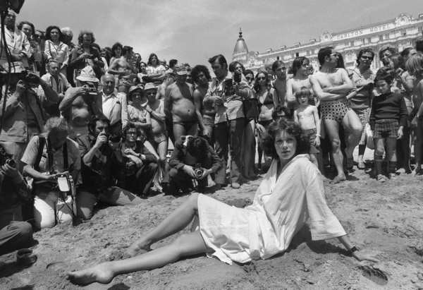 In May 1977, Sylvia Kristel poses on beach for press photographers and fans during Cannes Film Festival.