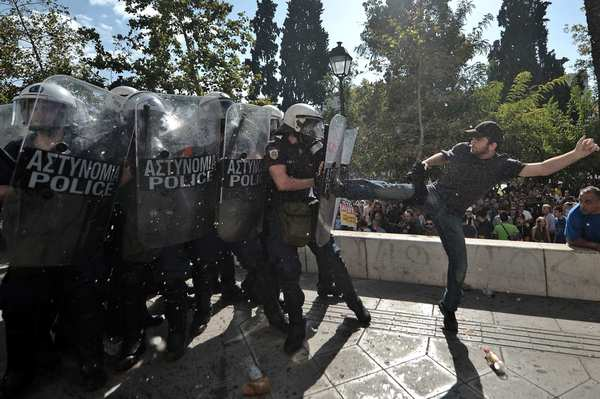 A demonstrator clashes with riot police during a 24-hour strike in Athens. Greek riot police fired tear gas to disperse protesters at an anti-austerity rally held during a national general strike as EU leaders were to tackle the eurozone crisis at a summit. The protesters had broken through a police line outside luxury hotels on central Syntagma Square and scattered groups of youths later attacked police with stones and firebombs, an AFP reporter said.