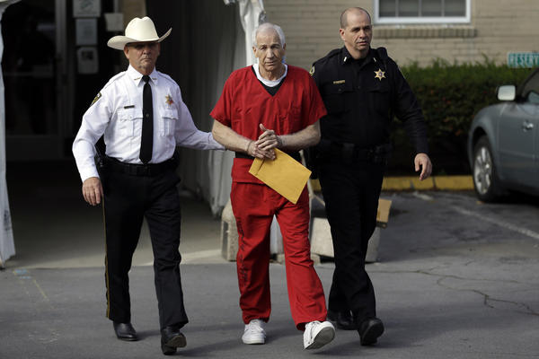 Former Penn State University assistant football coach Jerry Sandusky, center, is taken from the Centre County Courthouse by Centre County Sheriff Denny Nau, left, and a deputy, after being sentenced in Bellefonte, Pa., Tuesday, Oct. 9. Sandusky asked a judge on Thursday to overturn his child sexual abuse convictions and grant him a new trial, claiming his lawyers lacked sufficient time to prepare and the statute of limitations for some charges had expired.