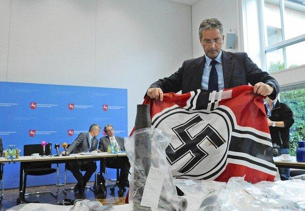 A police officer shows a Nazi flag at a Sept. 25 news conference in Hanover, Germany, that was confiscated from the neo-Nazi group Besseres Hannover, or Better Hanover.