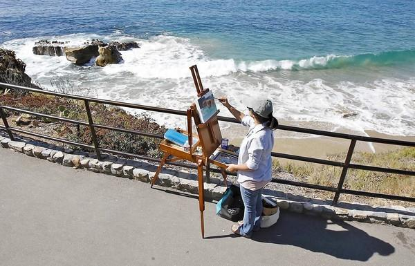 Caroline Scarbro paints a group of rocks below Monument Point as she participates in the LCAD Next Generation Paint-Off as part of the annual Laguna Art Museum's Plein Air Invitational at Heisler Park.
