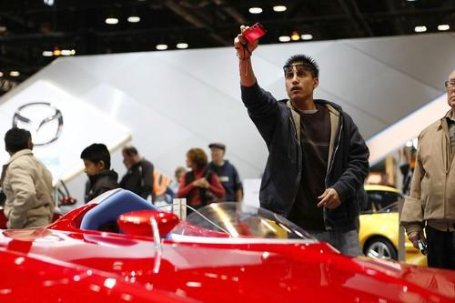 "George Vazquez, 19, of DesPlaines, photographs a concept Mazda Miyata Mono Posto one-person concept vehicle Sunday at the <a class=""taxInlineTagLink"" id=""EVFES0000003"" title=""Chicago Auto Show"" href=""/topic/economy-business-finance/chicago-auto-show-EVFES0000003.topic"">Chicago Auto Show</a>."